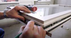майстер по ремонту металопластикових вікон встановлює нову фурнітуру